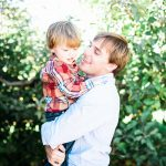 Father and Son hug in this portrait amongst the apple trees