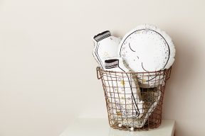 modern wire basket filled with cute kids cushions in the shape of moons and jars of stars