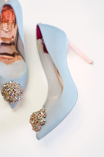 flatlay of the blue peetch shoes by ted baked with rose gold heels and insoles