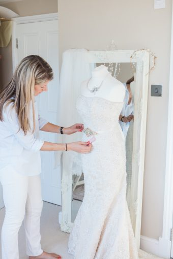 Victoria is working on a bridal sash on a mannequin
