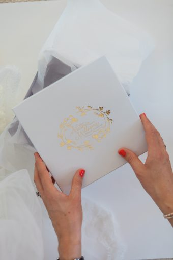 Victoria packaging on of her designs in a white box with gold foil and white tisse paper