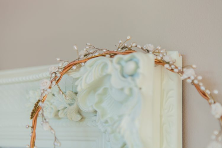 gold and pearl bridal headpiece perched on a white mirror frame