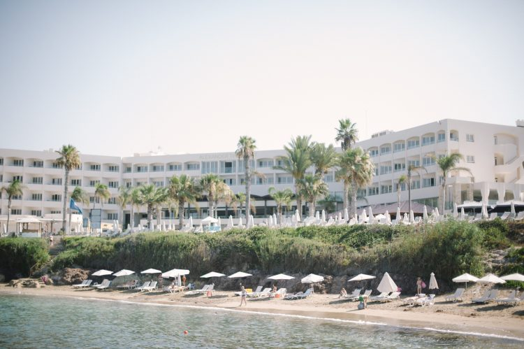 beach with sunloungers and the Alexander the Great hotel