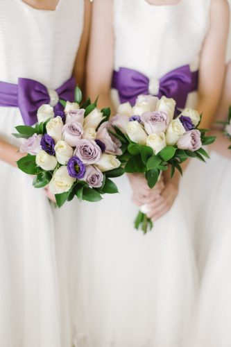 bridesmaids holding bouquets with cream and purple flowers and wearing a purple sash