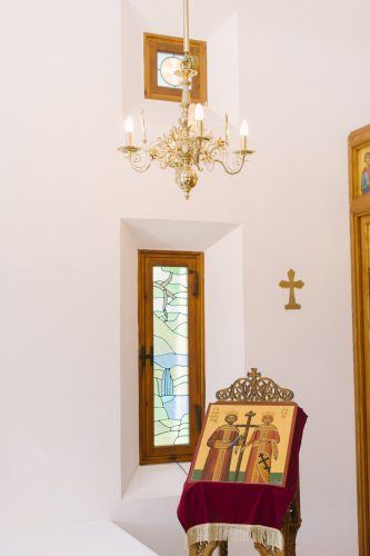 inside the small chapel with a brass chandelier
