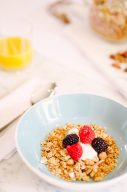 blue ceral bowl with granola and berries with orange juice on the side