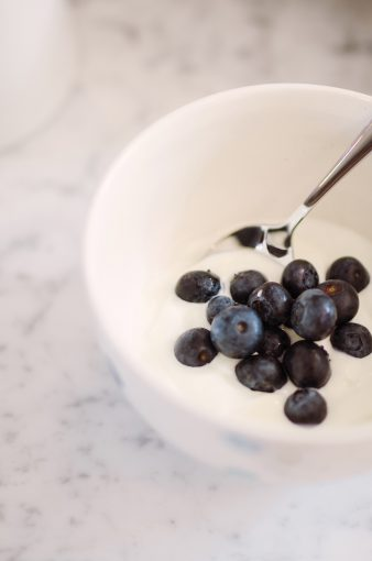 bowl of yoghurt and blueberries on a marble worktop
