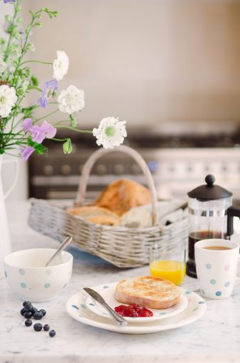 stylish breakfast scene with baskect of fresh bread, fresh toast and jam