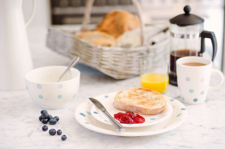 jam and toast breakfast with blueberries scattered frech orange juice and basket of bread