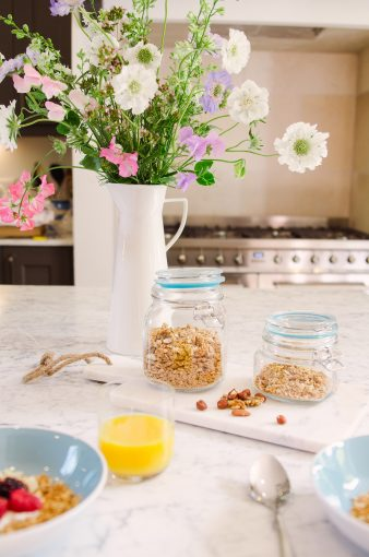 stylish kitchen breakfast scene with jars of granola and nuts