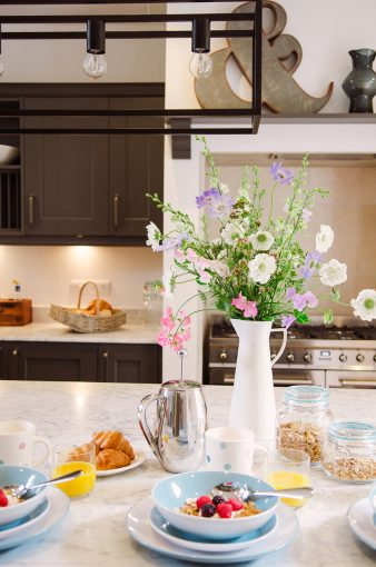 stylish kitchen with perfect breakfast scene with coffee and a beautiful display of flowers in a white jug