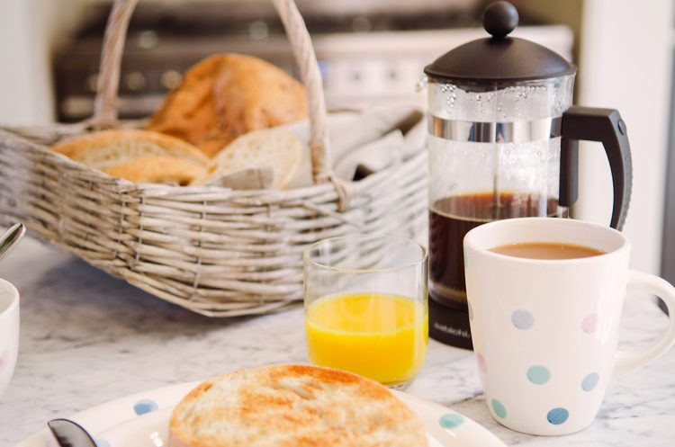 breakfast served with organge juice, basket of bread and french press coffee