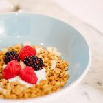 granola in a blue bowl topped with berries and yoghurt
