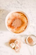 flatlay of hot chocolate with sieve of coco powder and marshmallows dusted with coco