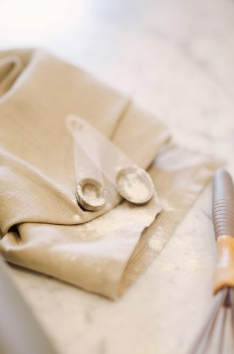 grey linen napkin with measuring spoons and covered in flour