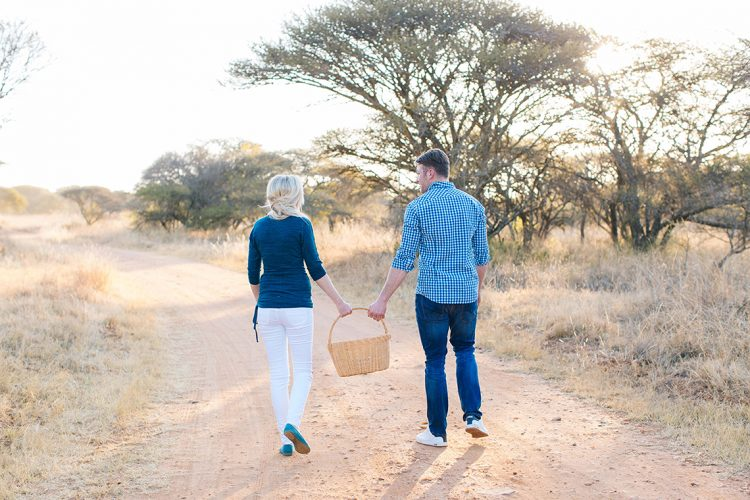 couple walking trough the nature reserve holding a picnic basket together