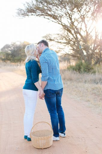 couple lean in for a kiss over the picnic basket