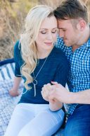 couple sit on a picnic blanket and hold hands