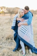 couple wrapped together in a patchwork blanket stood in golden grass