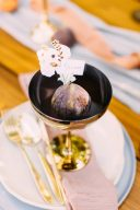 wedding place setting with fig in a golden glass