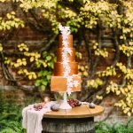 copper wedding cake with trailing leaves detail sat on top of a barrel