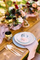 table setting with pink napkins gold cutlery and gold glassware