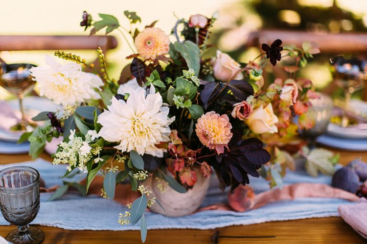 blue table runner with autumnal centrepiece and peach flowers