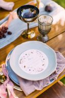 pretty wedding table setting with blue plates and round menu sat inside the dish
