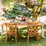wooden table setting under a tree with a floral centrepiece