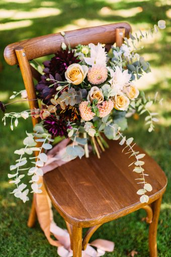 wooden chair with bouquet with peach flowers and eucalyputus