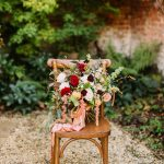 bouquet on a wooden chair outdoors with red flowers and peach silk ribbon
