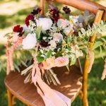 wooden chair with bouquet in autumn colours and peach ribbon