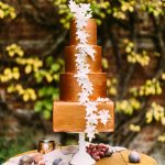 copper wedding cake with trailing leave displayed on top of a wooden barrel