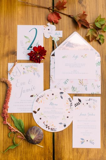 set of stationery and flowers displayed on a wooden background