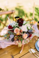 floral centrepiece on a pink runner and deep red flowers