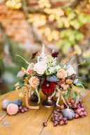 beautiful floral centrepiece in an urn with fruit displayed on the table beside it