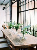 wooden table decorated with botanical centrepieces