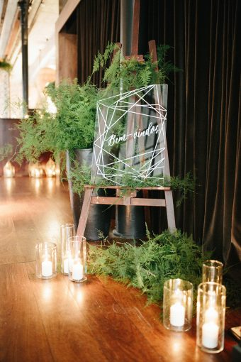 feature wedding sign with a geometric theme surrounded by stylish lanterns and green foliage