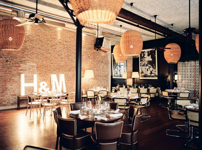 urban industrial chic venue with large statement light pendants exposed brick wall ad lit up initials