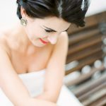 bridal look with statement earrings a chic updo hair and signature red lip colour