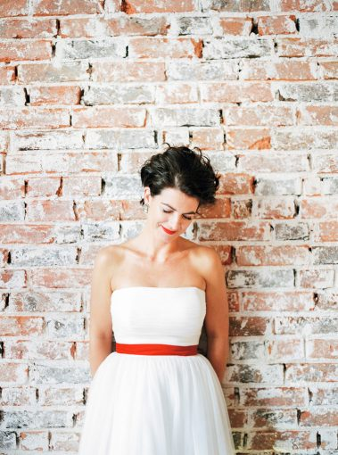 bride wearing a mid length dress with a red sash stood against a brick wall