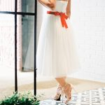 bride with her white mid length wedding dress, a red sash and statement sparkly heels