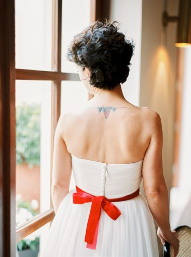 bride with her white wedding dress and simple red sash