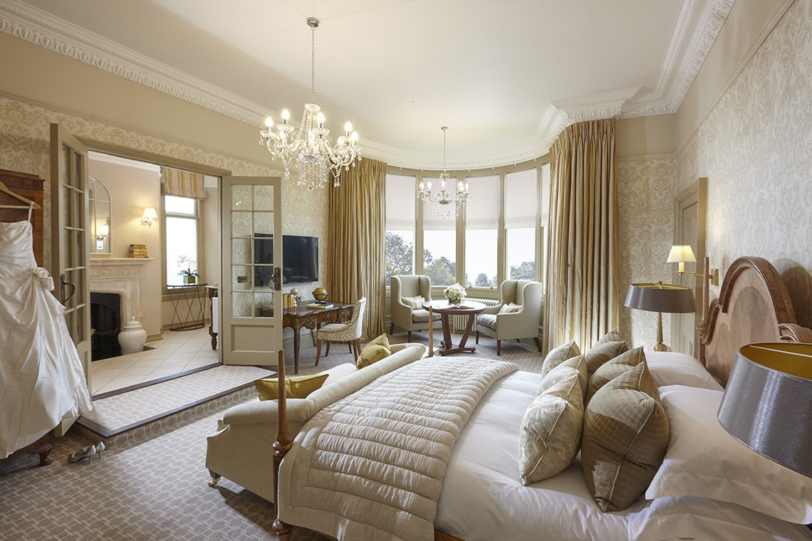 beautiful luxury hotel bedroom suite at clevedon hall with chandelier gold colour scheme and large bay window