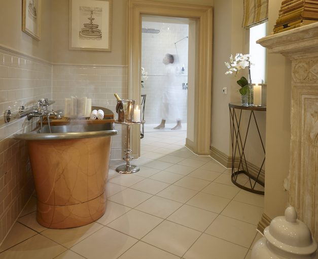 luxe bathroom at clevedon hall hotel with copper roll top bath