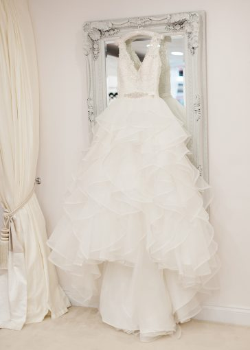 beautiful ruffled skirt wedding gown hung on a mirror