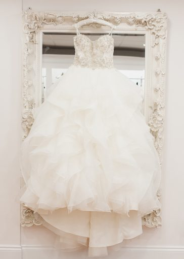 ruffled wedding dress hung on a beautiful mirror
