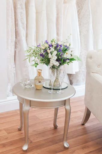 small table with champagne glasses and flower display