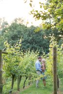 couple holding hands and stood amongst the vines