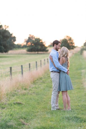 couple embrace as they stand in the beautiful fields